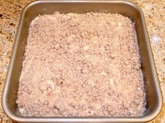 Crumb cake in pan with crumbs